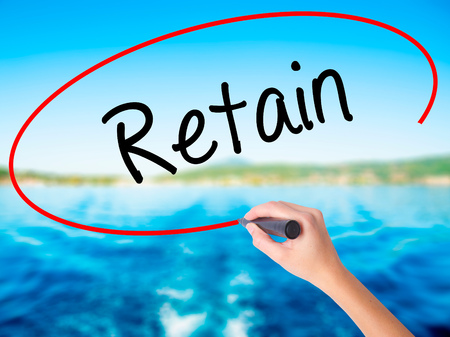 retained: Woman Hand Writing Retain on blank transparent board with a marker isolated over water background. Business concept. Stock Photo