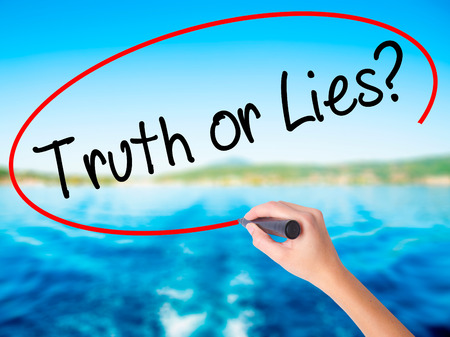 Woman Hand Writing Truth or Lies? on blank transparent board with a marker isolated over water background. Business concept. Stock Photo