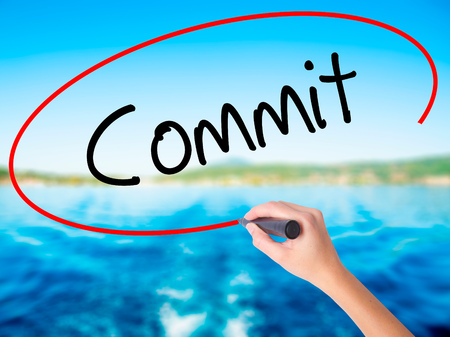commit: Woman Hand Writing Commit on blank transparent board with a marker isolated over water background. Business concept. Stock Photo