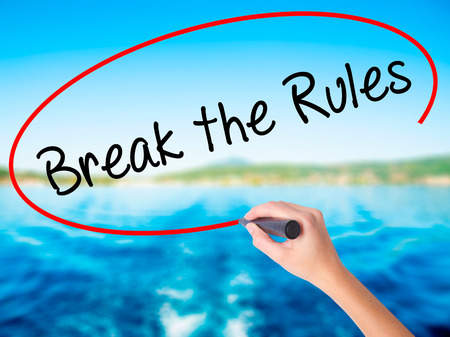 Woman Hand Writing Break the Rules on blank transparent board with a marker isolated over water background. Business concept. Stock Photo