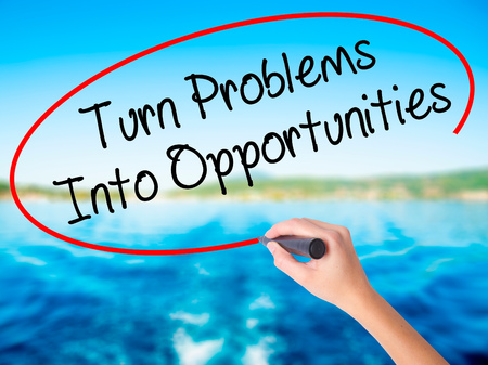 Woman Hand Writing Turn Problems into Opportunities on blank transparent board with a marker isolated over water background. Business concept. Stock Photo Stock Photo