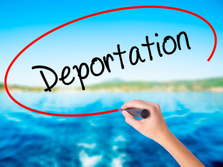deportation: Woman Hand Writing Deportation  on blank transparent board with a marker isolated over water background. Business concept. Stock Photo