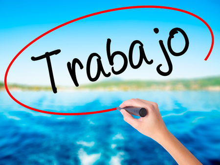 Woman Hand Writing Trabajo  ( work in Spanish) on blank transparent board with a marker isolated over water background. Business concept. Stock Photo