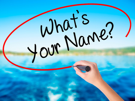 Woman Hand Writing Whats your Name? on blank transparent board with a marker isolated over water background. Business concept. Stock Photo