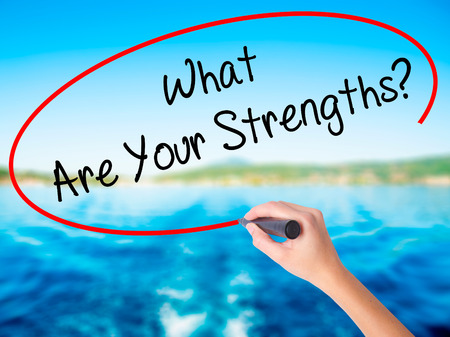 Woman Hand Writing What Are Your Strengths? on blank transparent board with a marker isolated over water background. Business concept. Stock Photo