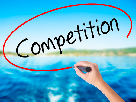 business pitch: Woman Hand Writing Competition  on blank transparent board with a marker isolated over water background. Business concept. Stock Photo