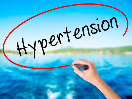 Woman Hand Writing Hypertension on blank transparent board with a marker isolated over water background. Business concept. Stock Photo