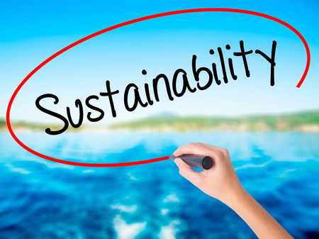 Woman Hand Writing Sustainability  on blank transparent board with a marker isolated over water background. Business concept. Stock Photo Stock Photo
