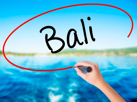 bali province: Woman Hand Writing Bali  on blank transparent board with a marker isolated over water background. Business concept. Stock Photo