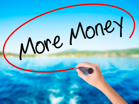 Woman Hand Writing More Money on blank transparent board with a marker isolated over water background. Business concept. Stock Photo