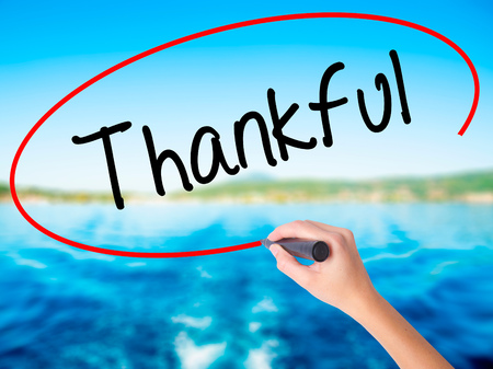 obliged: Woman Hand Writing Thankful  on blank transparent board with a marker isolated over water background. Business concept. Stock Photo