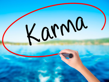 bad fortune: Woman Hand Writing Karma  on blank transparent board with a marker isolated over water background. Business concept. Stock Photo