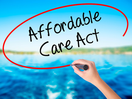 affordable: Woman Hand Writing Affordable Care Act on blank transparent board with a marker isolated over water background. Business concept. Stock Photo Stock Photo