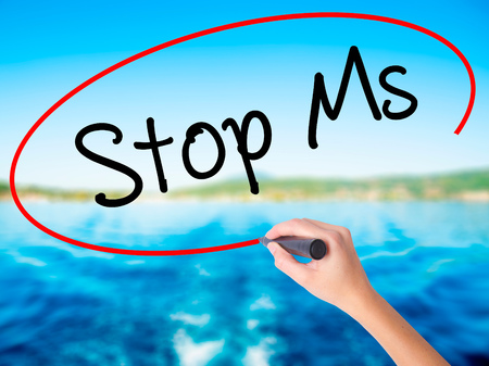 spasms: Woman Hand Writing Stop Ms on blank transparent board with a marker isolated over water background. Business concept. Stock Photo