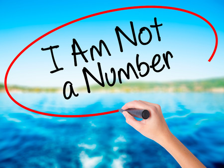 consumer rights: Woman Hand Writing I Am Not a Number on blank transparent board with a marker isolated over water background. Business concept. Stock Photo