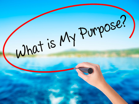 Woman Hand Writing What is My Purpose? on blank transparent board with a marker isolated over water background. Business concept. Stock Photo