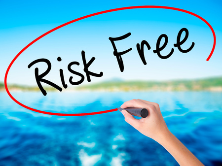 Woman Hand Writing Risk Free on blank transparent board with a marker isolated over water background. Business concept. Stock Photo
