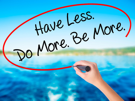 Woman Hand Writing Have Less. Do More. Be More.  on blank transparent board with a marker isolated over water background. Business concept. Stock Photo