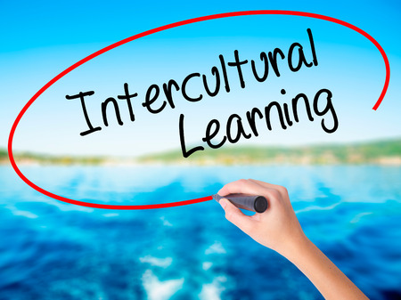 intercultural: Woman Hand Writing Intercultural Learning on blank transparent board with a marker isolated over water background. Business concept. Stock Photo