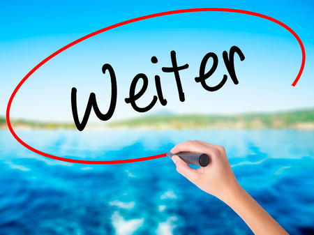 continue: Woman Hand Writing Weiter (Continue in German)  on blank transparent board with a marker isolated over water background. Business concept. Stock Photo Stock Photo