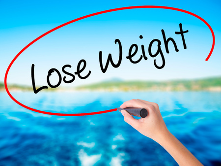 weightloss plan: Woman Hand Writing Lose Weight on blank transparent board with a marker isolated over water background. Business concept. Stock Photo