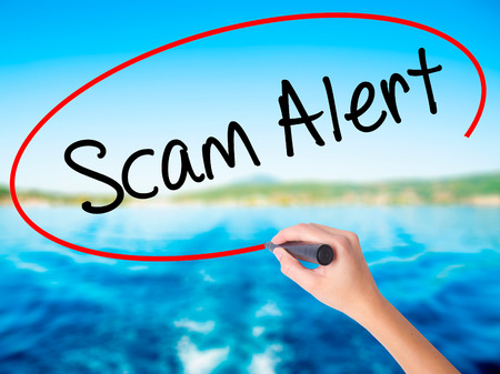 Woman Hand Writing Scam Alert  on blank transparent board with a marker isolated over water background. Business concept. Stock Photo