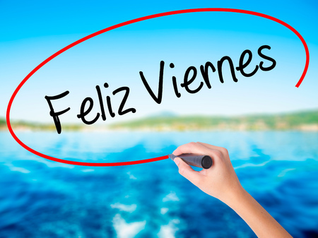 feliz: Woman Hand Writing Feliz Viernes (Happy Friday In Spanish)  on blank transparent board with a marker isolated over water background. Business concept. Stock Photo