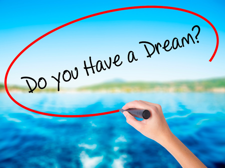 Woman Hand Writing Do you Have a Dream? on blank transparent board with a marker isolated over water background. Business concept. Stock Photo