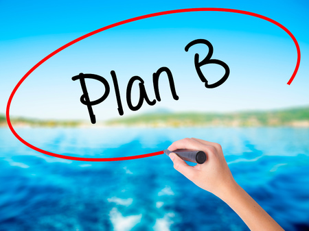 Woman Hand Writing Plan B on blank transparent board with a marker isolated over water background. Business concept. Stock Photo