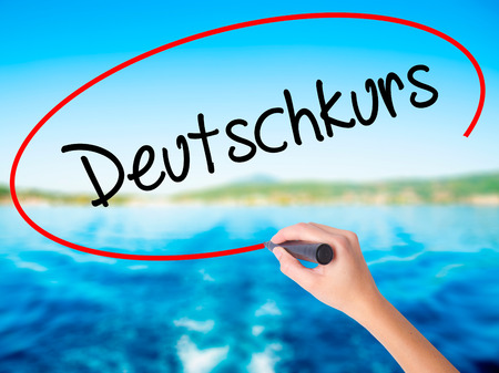 naturalization: Woman Hand Writing Deutschkurs (German Course in German) on blank transparent board with a marker isolated over water background. Business concept. Stock Photo Stock Photo