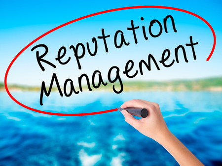 Woman Hand Writing Reputation Management on blank transparent board with a marker isolated over water background. Business concept. Stock Photo