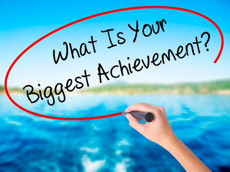 overachieving: Woman Hand Writing What Is Your Biggest Achievement? on blank transparent board with a marker isolated over water background. Business concept. Stock Photo Stock Photo