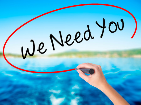 Woman Hand Writing We Need You on blank transparent board with a marker isolated over water background. Business concept. Stock Photo
