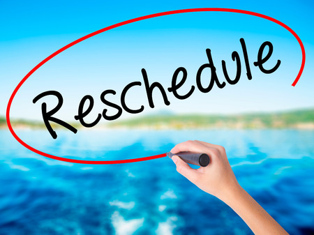 Woman Hand Writing Reschedule  on blank transparent board with a marker isolated over water background. Business concept. Stock Photo Stock Photo