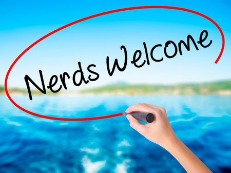 Woman Hand Writing Nerds Welcome on blank transparent board with a marker isolated over water background. Business concept. Stock Photo