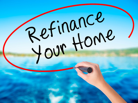 Woman Hand Writing Refinance Your Home on blank transparent board with a marker isolated over water background. Business concept. Stock Photo Stock Photo