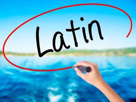 Woman Hand Writing Latin on blank transparent board with a marker isolated over water background. Business concept. Stock Photo