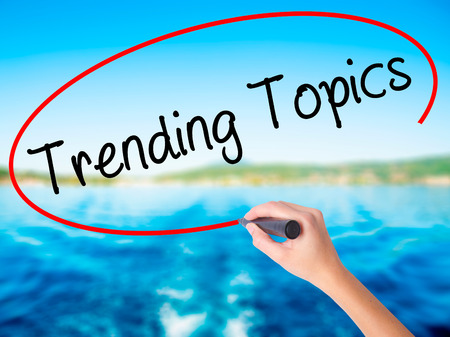 topics: Woman Hand Writing Trending Topics on blank transparent board with a marker isolated over water background. Business concept. Stock Photo