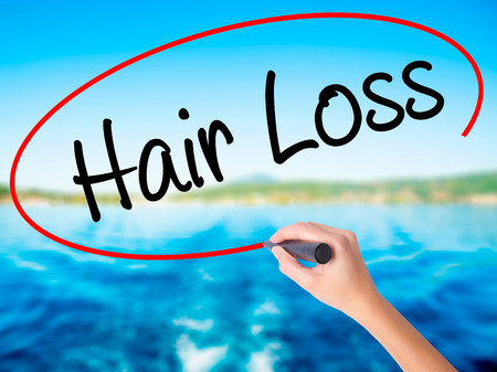calvicie: Woman Hand Writing Hair Loss on blank transparent board with a marker isolated over water background. Business concept. Stock Photo