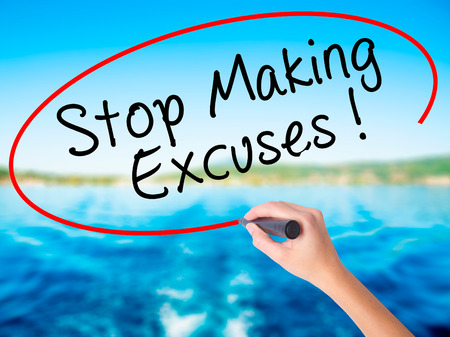 Woman Hand Writing Stop Making Excuses on blank transparent board with a marker isolated over water background. Business concept. Stock Photo