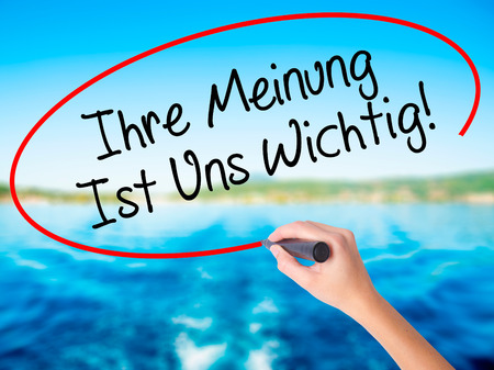 solicitation: Woman Hand Writing Ihre Meinung Ist Uns Wichtig! (Your Opinion is Important to Us in German) with marker on visual screen. Isolated on background. Business, technology, internet concept. Stock Photo