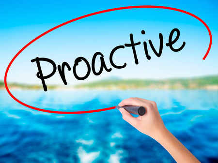 Woman Hand Writing Proactive on blank transparent board with a marker isolated over water background. Business concept. Stock Photo Stock Photo