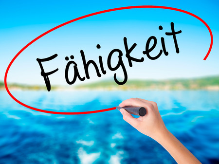 Woman Hand Writing Fahigkeit (Ability in German) on blank transparent board with a marker isolated over water background. Business concept. Stock Photo