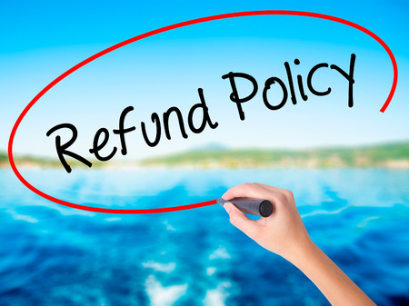 Woman Hand Writing Refund Policy on blank transparent board with a marker isolated over water background. Business concept. Stock Photo