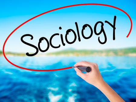 sociologia: Mujer escritura de la mano a bordo de Sociología transparente blanco con un marcador aislado sobre el fondo del agua. Concepto de negocio. Foto de stock