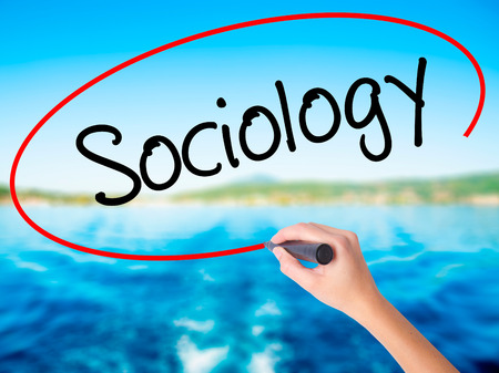 sociology: Woman Hand Writing Sociology  on blank transparent board with a marker isolated over water background. Business concept. Stock Photo