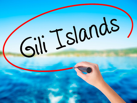 ferien: Woman Hand Writing Gili Islands on blank transparent board with a marker isolated over water background. Business concept. Stock Photo