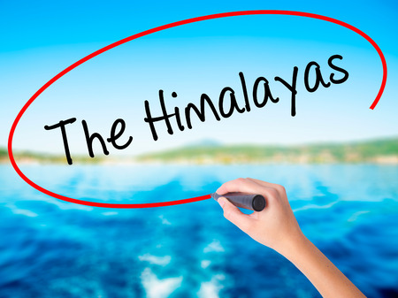 Woman Hand Writing The Himalayas on blank transparent board with a marker isolated over water background. Business concept. Stock Photo