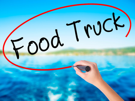 Woman Hand Writing Food Truck on blank transparent board with a marker isolated over water background. Business concept. Stock Photo Stock Photo