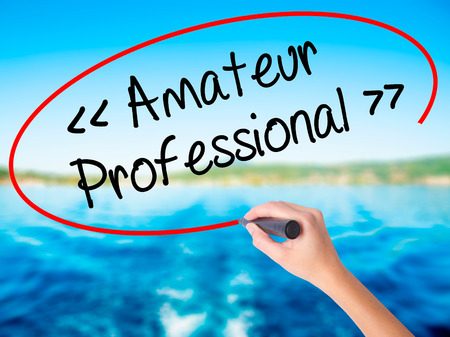 Woman Hand Writing Amateur - Professional with a marker over transparent board. Isolated on background. Business, technology, internet concept. Stock  Photo
